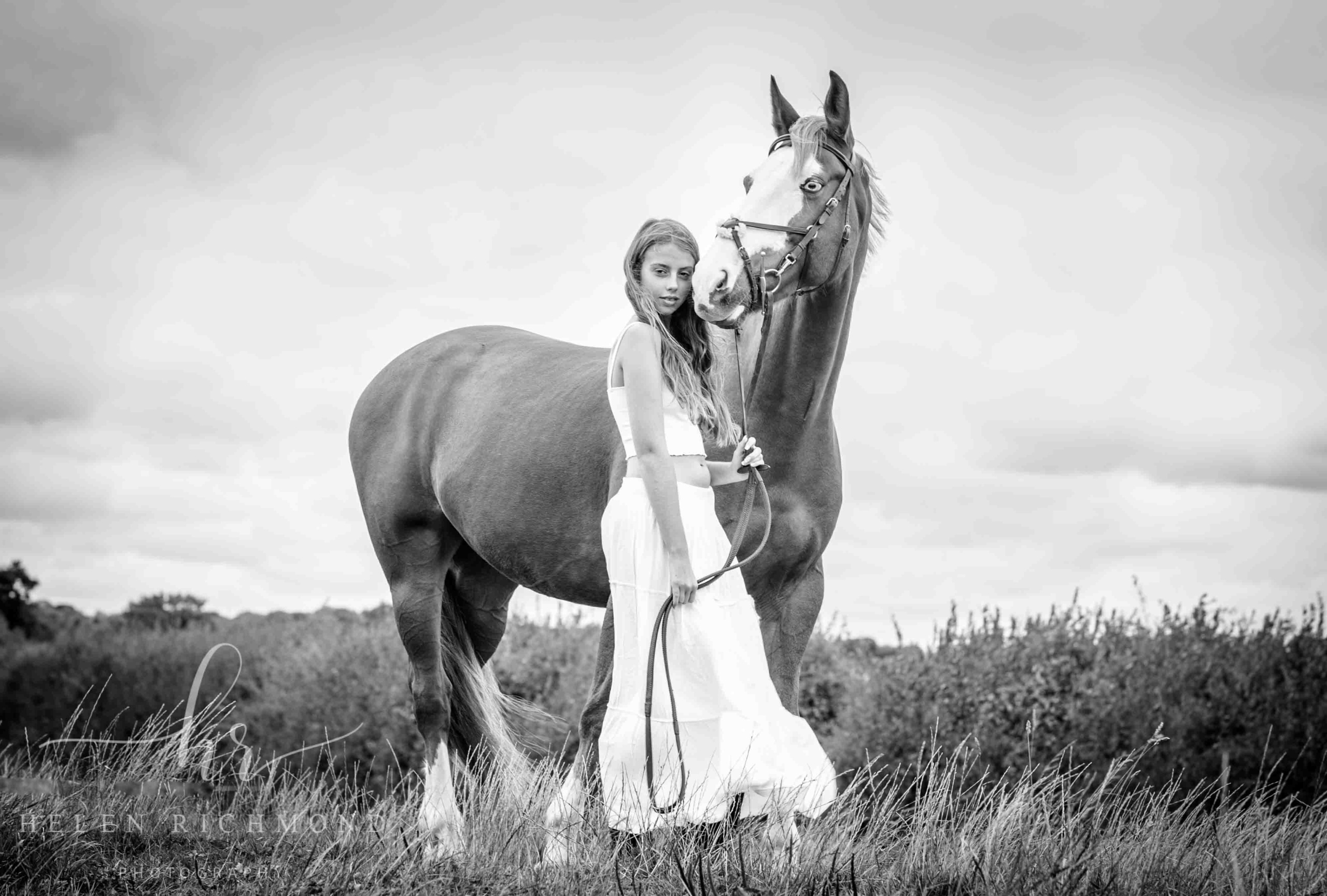 Horse Photography, black and white photograph of young women in white dress stood alongside horse set in landscape setting